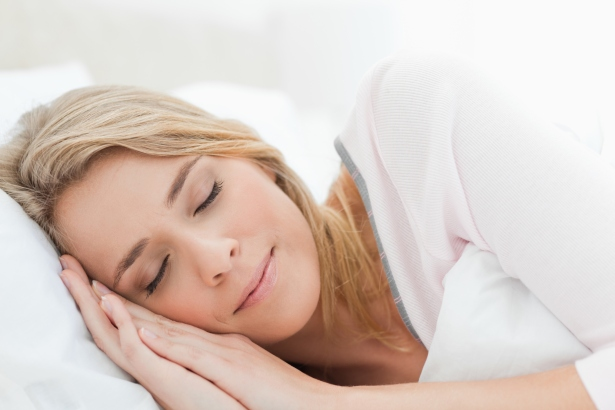 Woman sleeping in bed her head resting on a pillow and hands beside her face