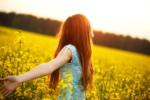 Young woman enjoying sunlight with raised arms in canola field