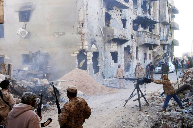 Members of the Libyan pro-government forces, backed by the locals, with weapons are seen during clashes in the streets with Shura Council of Libyan Revolutionaries in Benghazi